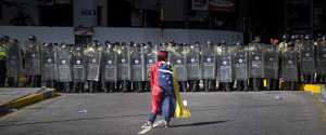 A demonstrator wearing a Venezuelan flag stands in front of police dressed in riot gear during a protest in Caracas, Venezuela, on Saturday, Jan. 24, 2015. Photographer: Wilfredo Riera/Bloomberg via Getty Images